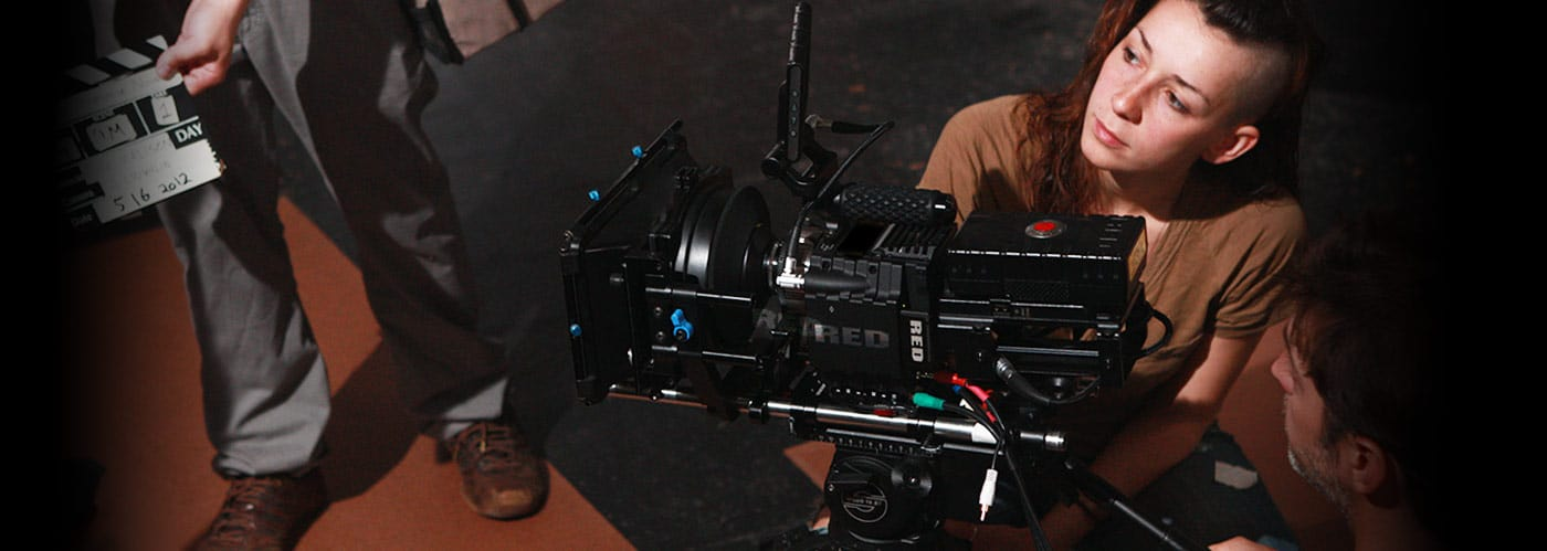 Two people are operating a large camera. A person is standing in front of them holding a clapper board.