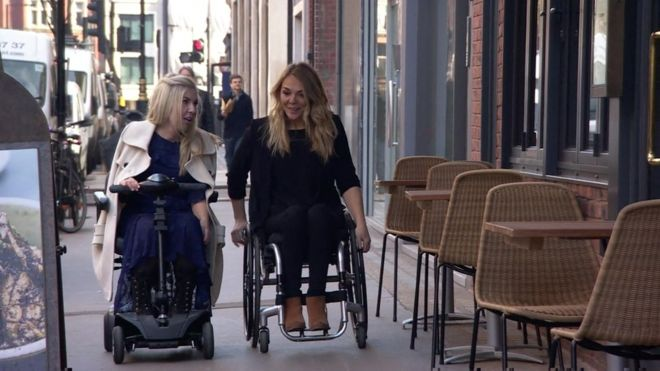 One person using an electric scooter and one person using a wheelchair make their way along a sidewalk, they are conversing.