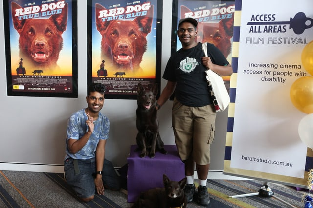 Two people that appear to be from CALD backgrounds stand in front of several Red Dog posters on a wall. One person is patting a dog that is sitting on a podium in front of the posters. There is also a dog at their feet.