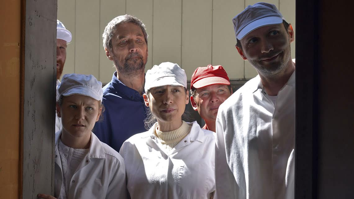 Six people are peering through a doorway. Four of the people are wearing white overalls and white hats. One person is wearing a red hat and one person is wearing a blue shirt and no hat. Each person has a different expression.