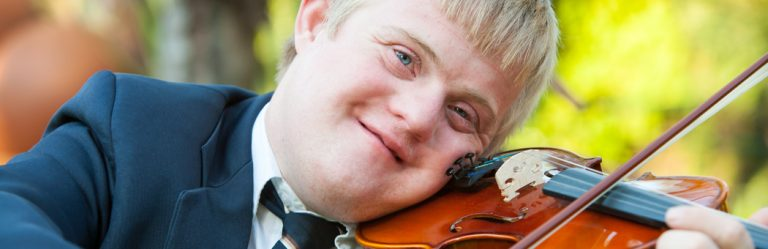 A person with Down Syndrome plays the violin.