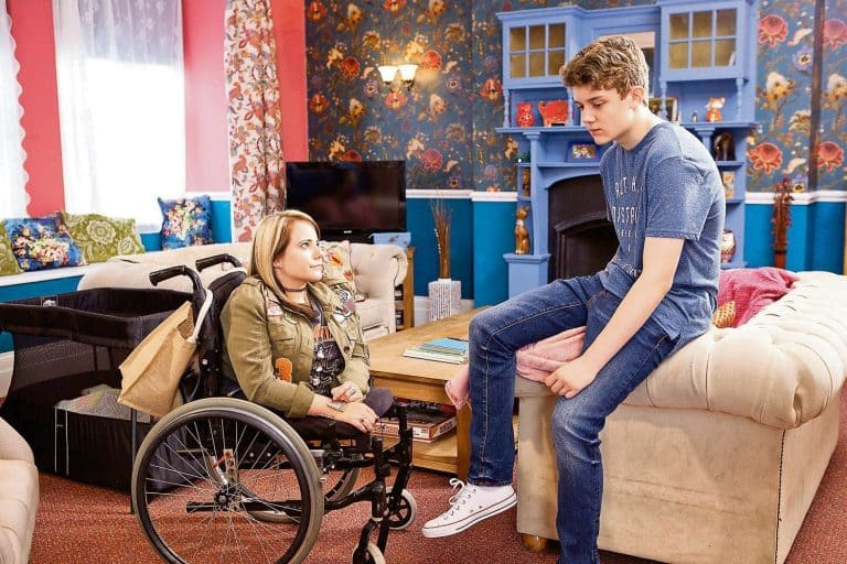 Two teenagers are in what appears to be a TV set livingroom. One person is leaning on a couch and the other is using a wheelchair.