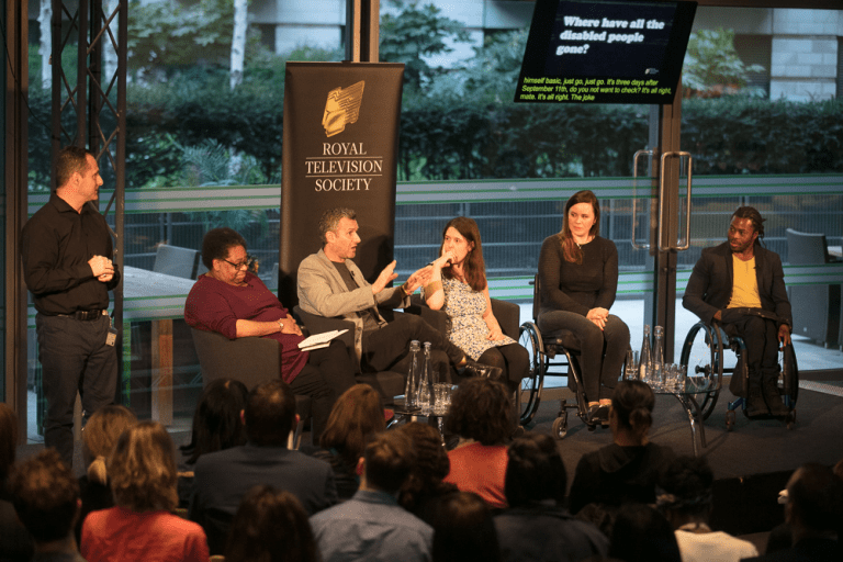 Six people are on a stage addressing an audience. Three people are wheelchair users. One person is standing and is possibly a sign language interpreter.