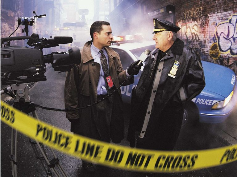 "Two people stand in a graffitied alleyway in front of a police car. One person is a police officer, the other is a reporter. The reporter is holding a microphone. There is a camera to the left of screen and caution tape across the entire image saying ""Police line do not cross""."