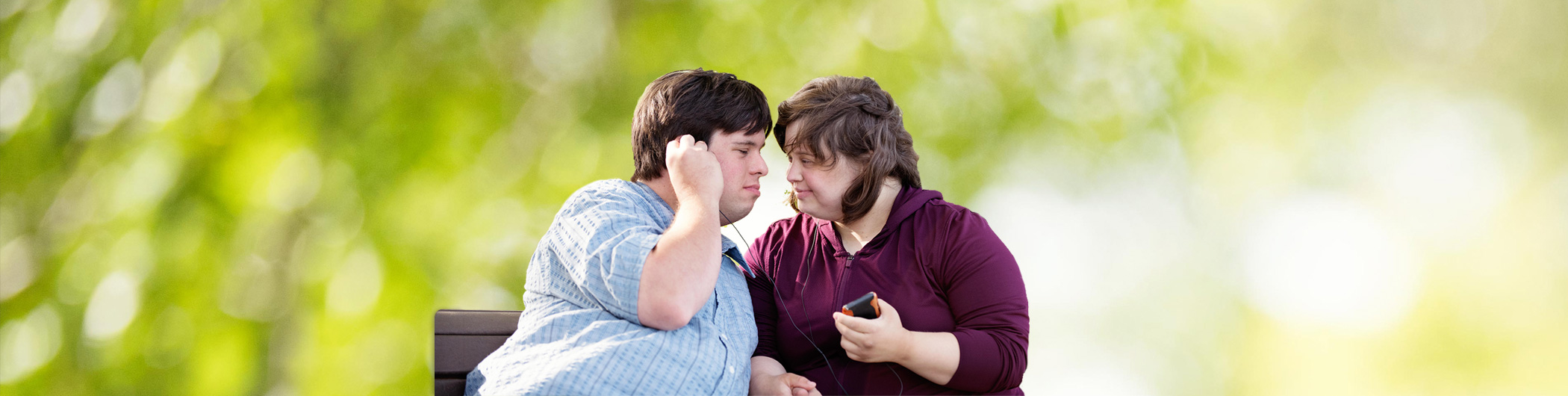 Two people with Down Syndrome sit on a park bench and listen to music together. They are looking at each other in a romantic way.