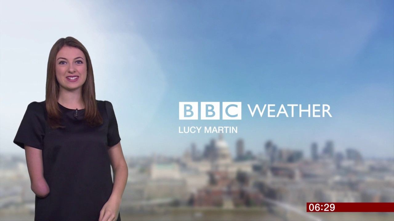 "A person with long brown hair and limb difference on their right arm stands to the left of the image, facing the camera. The words ""BBC weather"" and ""Lucy Martin"" are displayed to the right of the screen. The background is cloudy."