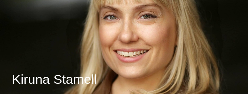 "A close up image of a person smiling at the camera with the words ""Kiruna Stamell"" displayed to the left of the screen."