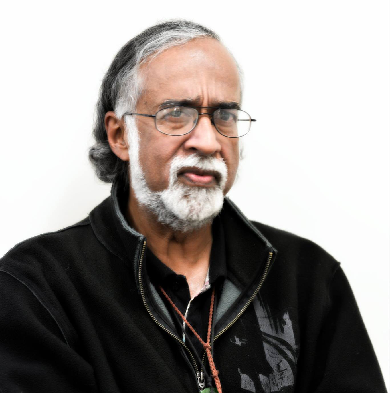 A person with dark skin and grey hair and facial hair looks sternly at the camera while wearing glasses.