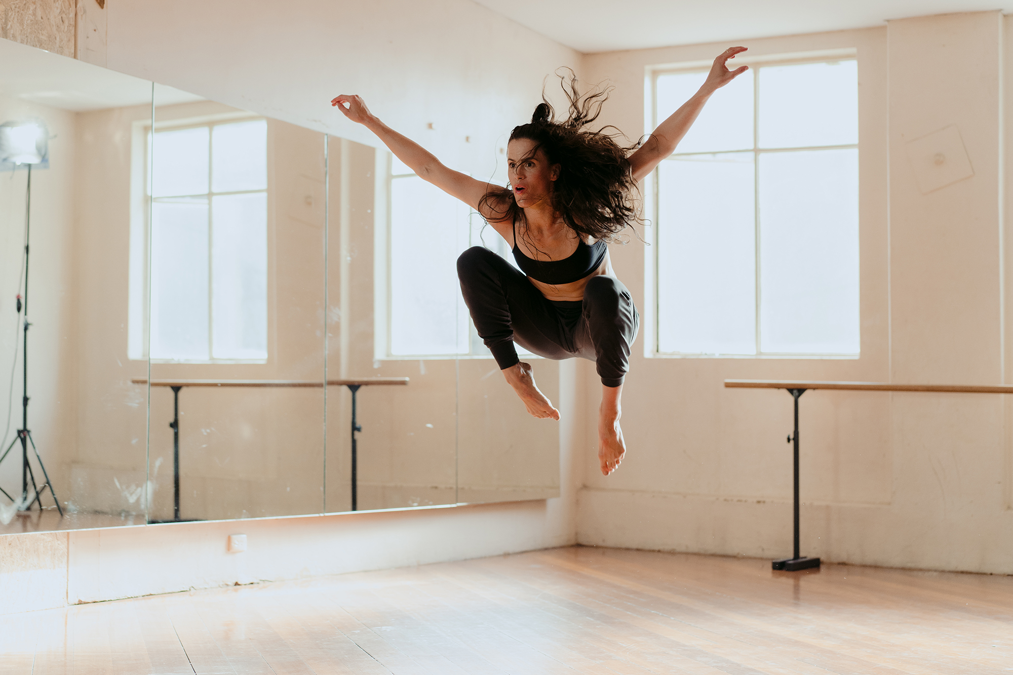A female in a bright dance studio jumping energetically in the air